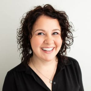 Kristin Financial Coordinator for Cardall Orthodontics; middle-aged woman with black curly hair wearing black scrubs