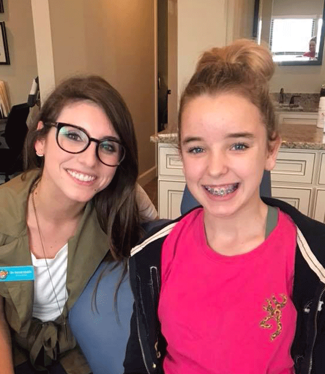 Young girl smiling wearing a pink shirt sitting next to a woman smiling wearing glasses and a green jacket