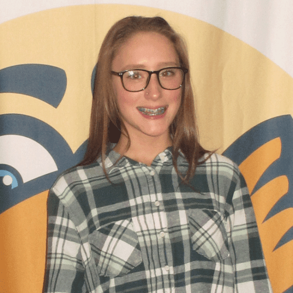Young girl smiling with braces wearing glasses and a plaid shirt