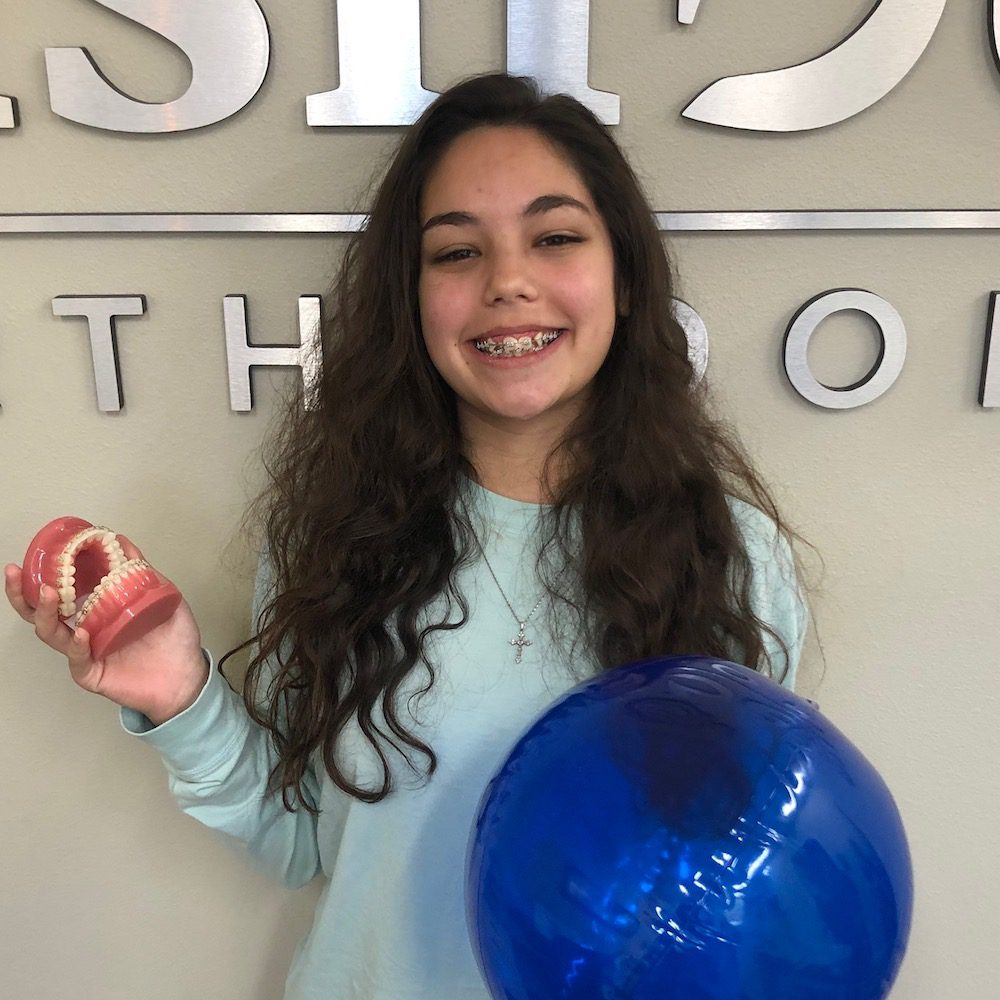 Jocelyne, EmBraces Anti-Bullying Ambassador of Fishbein Foundation, young girl smiling in front of Fishbein Orthodontics office, free orthodontic treatment