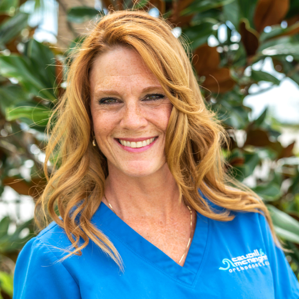 Woman with curly orange hair smiling wearing a blue shirt
