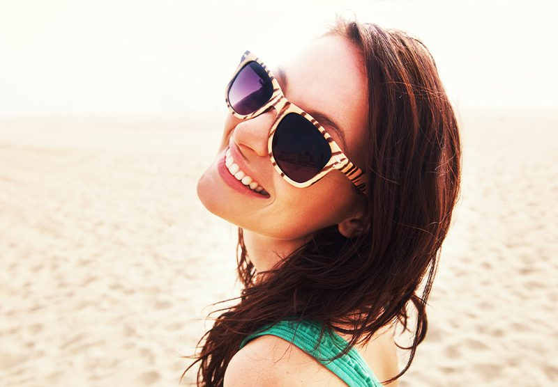 Young girl smiling on beach with Invisalign at Caudill & McNeight Orthodontics, How Braces Work