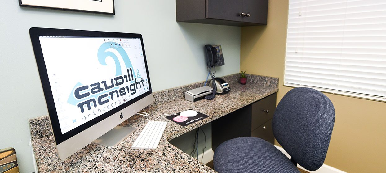 Caudill & McNeight Orthodontics office, New Year, New Website, office chair and computer screen with logo